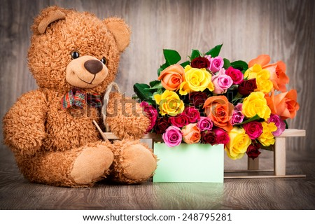 Roses and a teddy bear on wooden background - stock photo