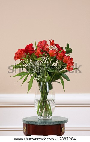 Roses and Alstroemeria on a marble stand in a crystal vase. - stock photo