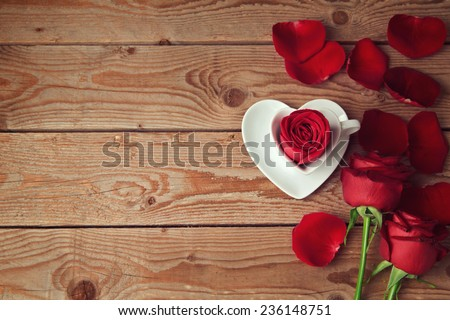 Roses and flower petals on wooden background with copy space. Valentine's day concept - stock photo