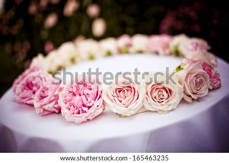 Roses and peonies bridal wreath on white cloth - stock photo