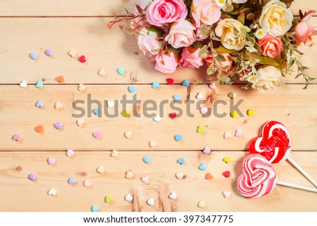 Roses flowers  with heart shape candy on wooden background Pastel color tone - stock photo