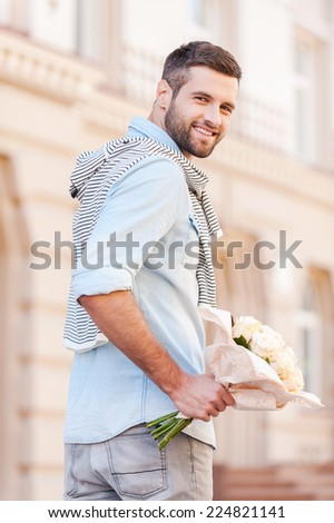 Roses for her. Rear view of cheerful young man holding bouquet of flowers and looking over shoulder while walking by the street  - stock photo