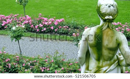 Roses in a large garden. In the foreground, a plaster figure.