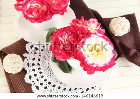 Roses in cups on napkins on wooden background