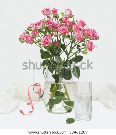 Roses in jug and a glass with water