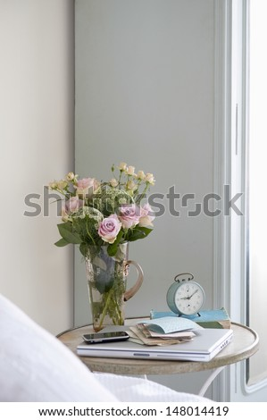 Roses in vase on bedside table with books and alarm clock in bedroom - stock photo