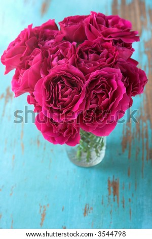 Roses in vase on rustic table - stock photo