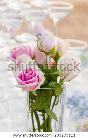 Roses on a dining table at a beach wedding ceremony - stock photo