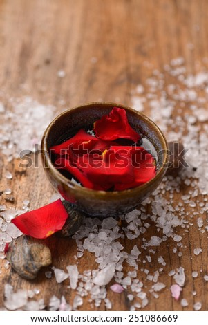 roses petals in bowl with pile of salt ,stones on old wooden board