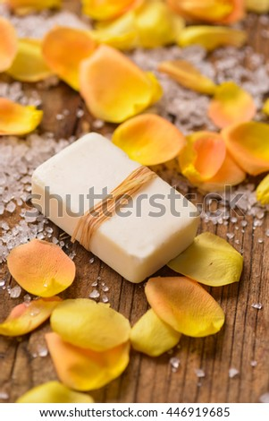 roses petals with pile of salt ,soap on old wooden
