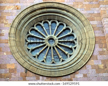 rosette or circular window filled with stained glass and ornamentation in the facade of one of the churches in Bolzano, Italy - stock photo