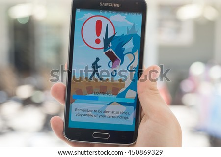 Roseville, CA/USA - July 11: An Android user reads the warning screen for the new Pokemon Go app that was released on July 6, 2016. It is an augmented reality mobile game for smart phones by Niantic - stock photo