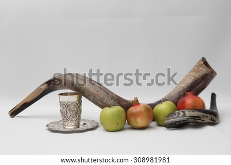 rosh hashanah (jewesh holiday) concept - shofar , Kiddush cup , honey, apple and pomegranate over White background . traditional holiday symbols.