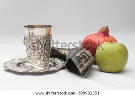 rosh hashanah (jewesh holiday) concept - shofar , Kiddush cup , honey, apple and pomegranate over White background . traditional holiday symbols. - stock photo