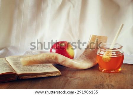 rosh hashanah (jewesh holiday) concept - shofar, torah book, honey, apple and pomegranate over wooden table. traditional holiday symbols.  - stock photo
