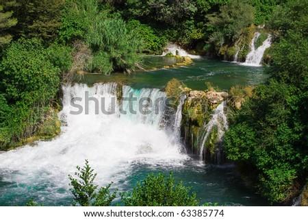 Roski Slap - Krka National Park (Croatia) River cascading through the forest between trees. - stock photo