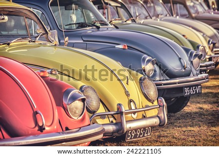 ROSMALEN, THE NETHERLANDS - JANUARY 4, 2015: Retro styled image of a row of vintage Volkswagen Beetles from the seventies in Rosmalen, The Netherlands - stock photo