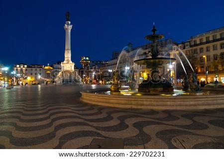 Rossio square and bronze fountain by night in la Baixa, Lisbon, Portugal - stock photo