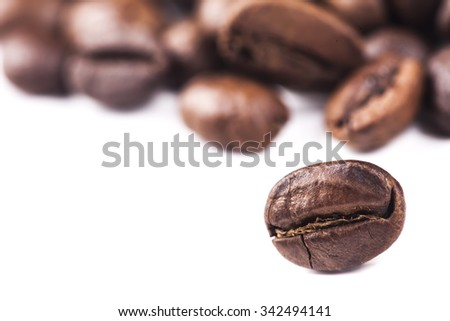 Rosted brown coffee beans lying on white background, selective focus, closeup