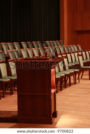 Rostrum with microphones and glass of water in empty auditorium. Prepared to business meeting - stock photo
