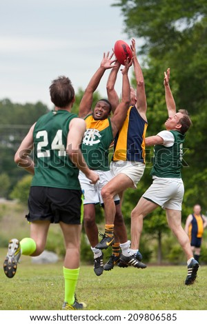 ROSWELL, GA - MAY 17:  Players jump and compete for the ball in an amateur game of Australian Rules Football in a Roswell city park, on May 17, 2014 in Roswell, GA.  - stock photo
