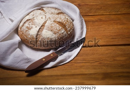 Rosy loaf of bread wrapped in white linen towel lying on a wooden table - stock photo