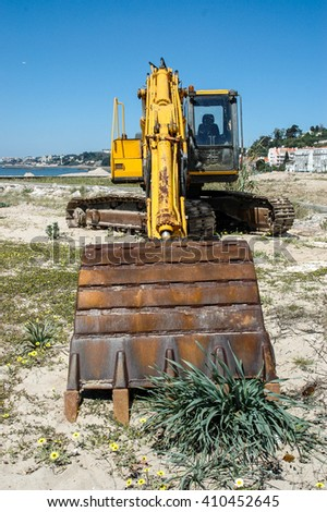 Rotary excavator on a beach with plants - stock photo