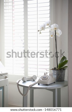 Rotary phone off the hook on a side table by shutter window - stock photo