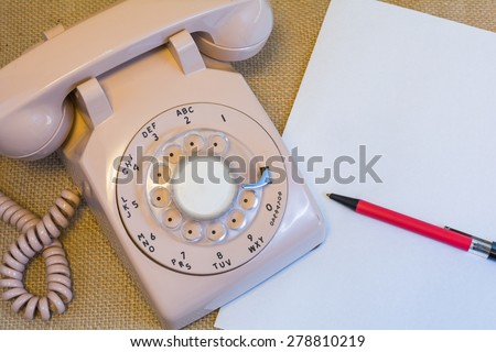 Rotary phone with blank paper and pen. - stock photo