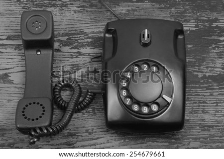 Rotary telephone on wooden background - stock photo