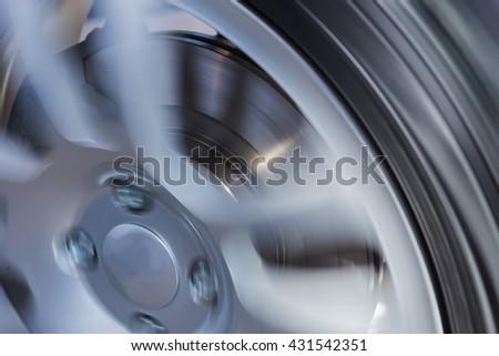 rotating car wheel and brake disc close up - stock photo