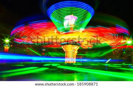 Rotating carousel in the fun park - stock photo