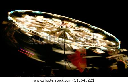 rotating fair ride at night with long exposure - stock photo