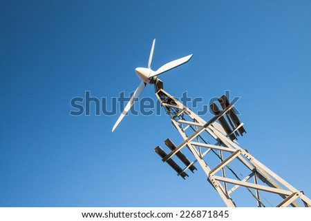 rotating small wind generator on a mast in front of a blue sky  - stock photo