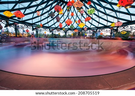 Rotating tea cups attraction in a Luna Park. - stock photo