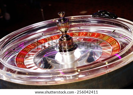 Rotating transparent roulette wheel in casino made of synthetic glass - stock photo