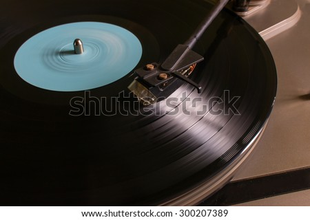 Rotating vinyl record with a blue mark on the turntable selective focus - stock photo