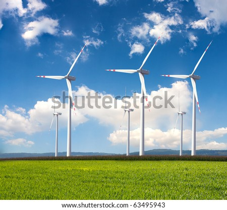 rotating wind turbine in front of cloudy sky - stock photo