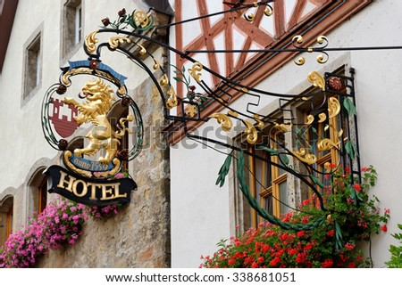 ROTHENBURG OB DER TAUBER, GERMANY - AUGUST 10, 2015: A hotel wrought iron hanging sign in Rothenburg, one of the best-preserved medieval towns in Europe, part of the famous Romantic Road tourist route - stock photo
