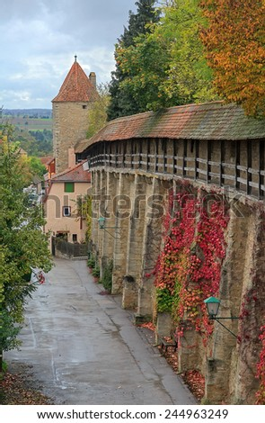Rothenburg on Tauber castle wall and tower with autumn vines and trees  - stock photo