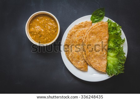 Roti and chicken curry. Top view on black background
