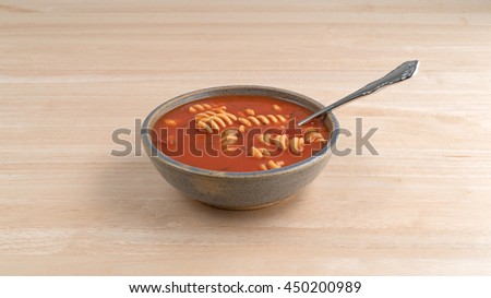 Rotini tomato soup in an old stoneware bowl with a spoon on a wood table top. - stock photo