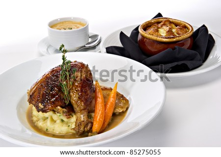 Rotisserie roasted chicken leg served over mashed potatoes with baby carrots and a gravy sauce.  A fresh green sprig of rosemary tops this off.  Warm bowls of soup are featured in the background. - stock photo