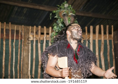 ROTORUA, NEW ZEALAND; APRIL 23: Maori man  with traditionally tatooed face and in traditional dress talks to group of tourists at Maori Culture, Tamaki Cultural Village, Rotorua, New Zealand. - stock photo