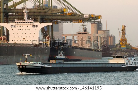 ROTTERDAM - JULY 08: A canal vessel and a bulkcarrier on July 08, 2013 in Rotterdam, Holland. The port of Rotterdam plays a main role in the international transfer and transit of ore deposits  - stock photo