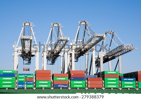 ROTTERDAM - MAR 8, 2011: Container cranes loading a ship in the port of Rotterdam. This port is the Europe's largest and facilitate the needs of a hinterland with 40,000,000 consumers. - stock photo