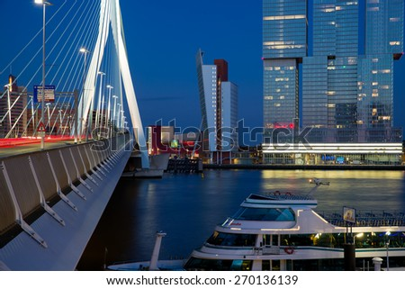 ROTTERDAM, NETHERLANDS - APRIL 6: Composition of erasmus bridge, KPN building and De Rotterdam designed by Rem Koolhaas at dusk with a cruise boat in the front, on April 6, 2015 in Rotterdam, Netherlands - stock photo