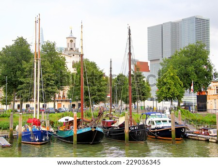 ROTTERDAM, NETHERLANDS - AUGUST 9, 2014: View of the three sailing boats at the background of the modern office building. - stock photo