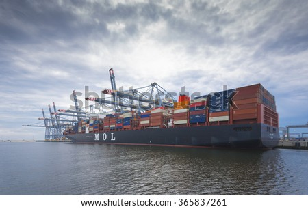 ROTTERDAM, NETHERLANDS - JUNE 28, 2015: Container ship being loaded in the Rotterdam harbor. Rotterdam is the largest harbor in Europe. - stock photo