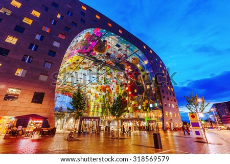 ROTTERDAM, NETHERLANDS - SEPTEMBER 03, 2015: modern market hall in Rotterdam at night. It was opened Oct 1, 2014 by Queen Maxima, designed by architect firm MVRDV. With unidentified people - stock photo